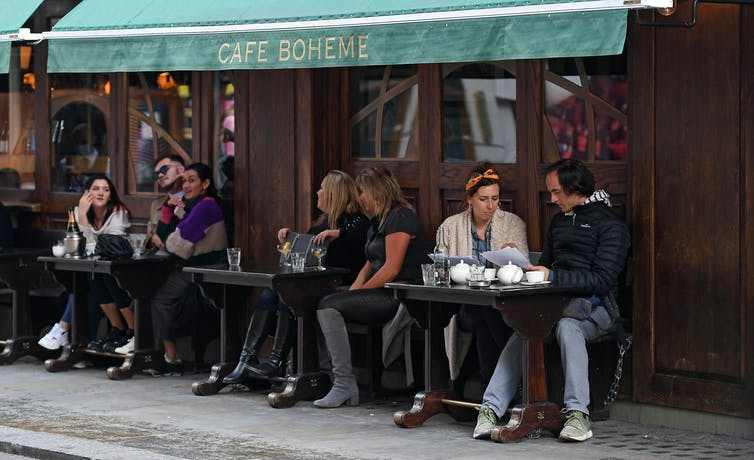 People drinking at tables outside a bar