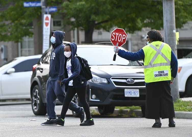 Two children cross the street; behind them a cross guard in a yellow vest holds up a stop sign.