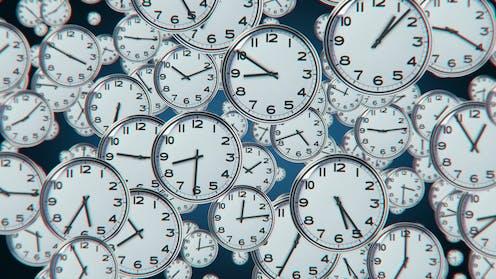 Muchos relojes marcando horas diversas flotando en el aire.