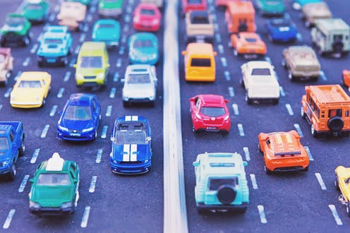 Model cars lined up bumper-to-bumper on a toy highway.