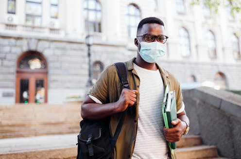 An African-American man wearing a mask walks down a flight of stairs while caring books.
