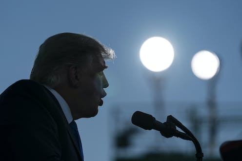 Donald Trump is seen in profile in the twilight with two shining lights in the background and microphone in front of him.