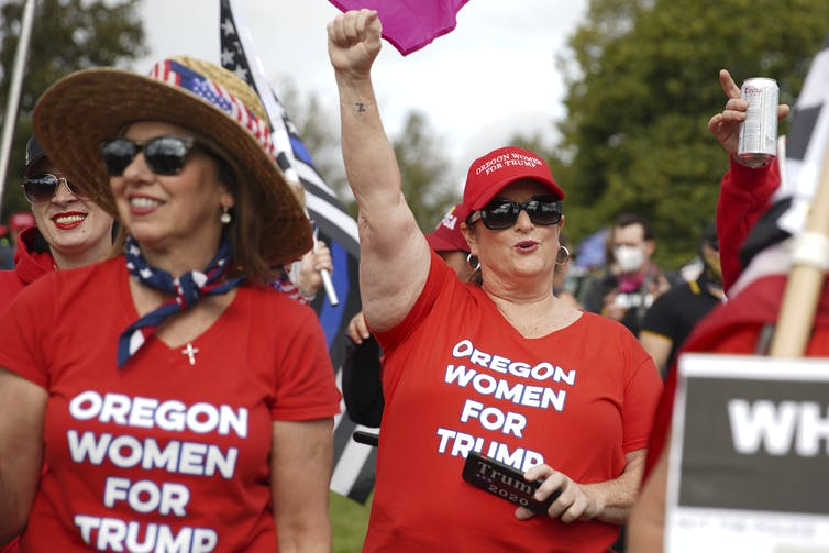Two women are cheering as they wear red T-shirts with the words Oregon Women For Trump