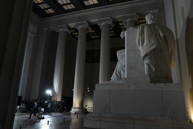 The Lincoln Memorial is in the foreground as TV lights illuminate a sitting Donald Trump