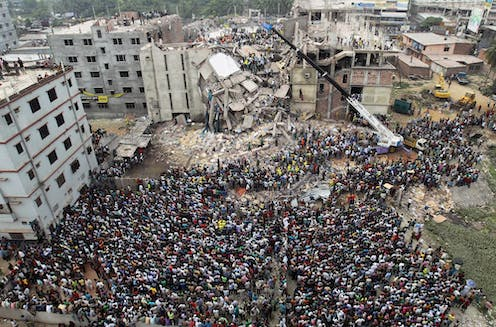 Hundreds of people are seen in an aerial shot in front of a collaposed multi-storey building.