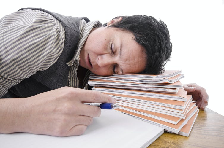 Exhausted female academic rests head on pile of assignments