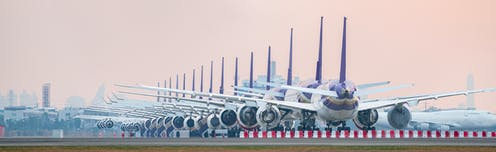 A row of grounded aeroplanes on an airport runway.