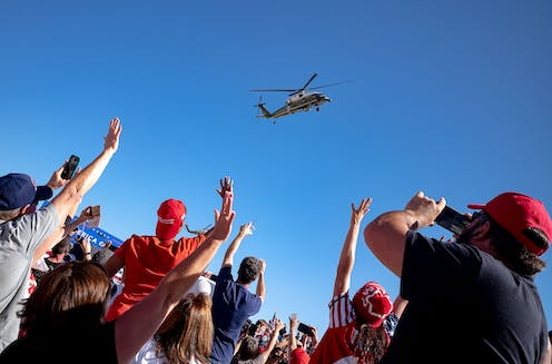 Trump rally attendees wave to his helicopter as he leaves.