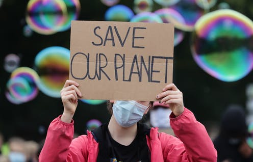 A young protester wearing a mask holds a sign saying 'save our planet'.