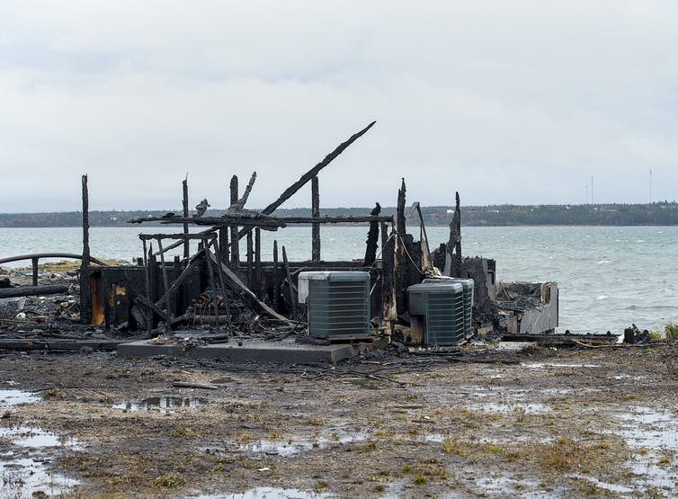 Debris from a burnt building next to the ocean.