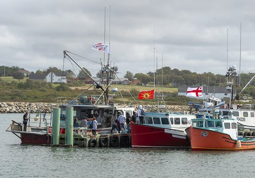 Fishing boats flying flags at dock and preparing to launch.