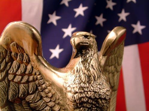 A bronze eagle and a U.S. flag