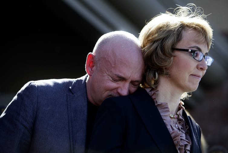 Kelly, crying, rests his head on Gabby Giffords' shoulder.