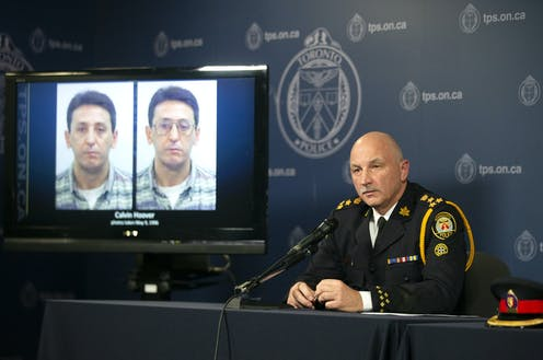 Police chief James Ramer sits in front of a TV screen displaying two mugshots of Calvin Hoover