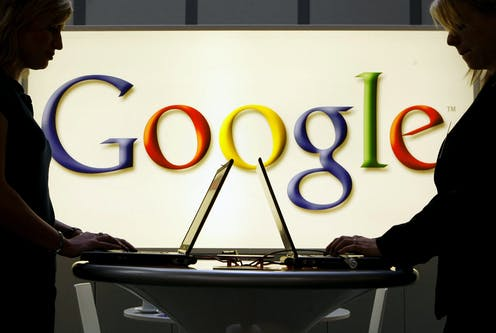 Google logo behind people working on computers.