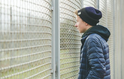 Teenage boys looking at sports field through the fence.