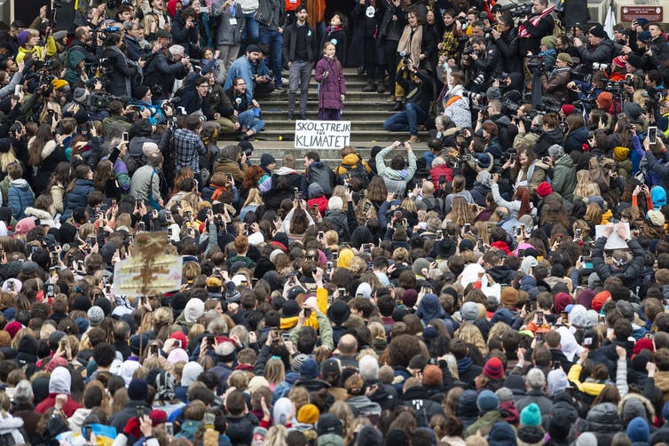 Thunberg speaks surrounded by a large crowd.