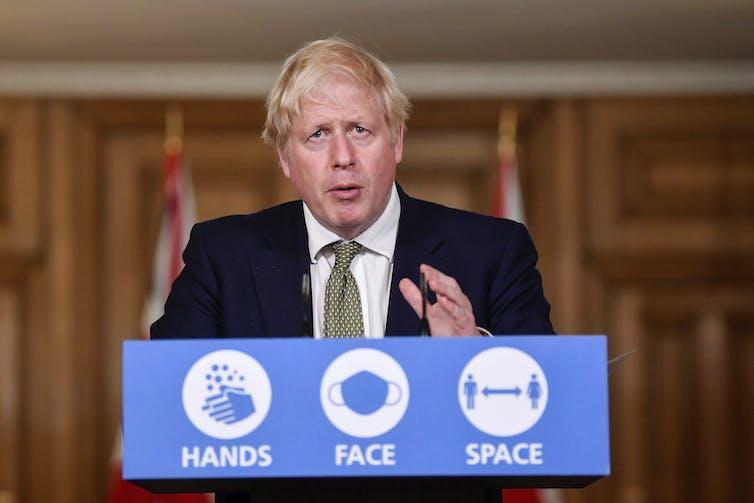 UK PM Boris Johnson at a speaker's podium.