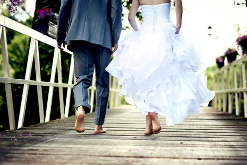Bride and groom barefoot on a wooden deck or jetty