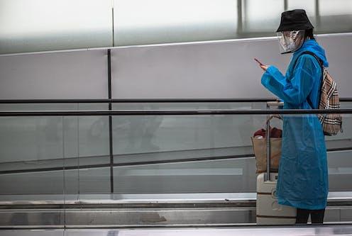 Una mujer con maletas, sombrero, mascarilla y pantalla facial mira el móvil en una cinta transportadora de nodo de transportes.