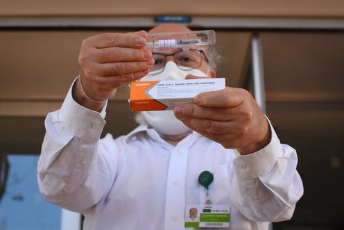Man in a lab coat holds up a dose of Sinovac's coronavirus vaccine.