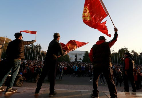 Supporters of Kyrgyzstan's new president Sadyr Japorov on the streets waving the national flag.
