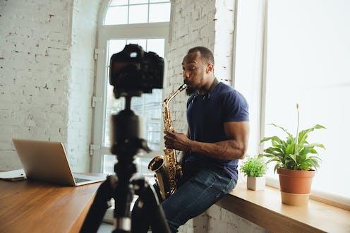 Un saxofonista toca el instrumento ante una cámara y un ordenador.