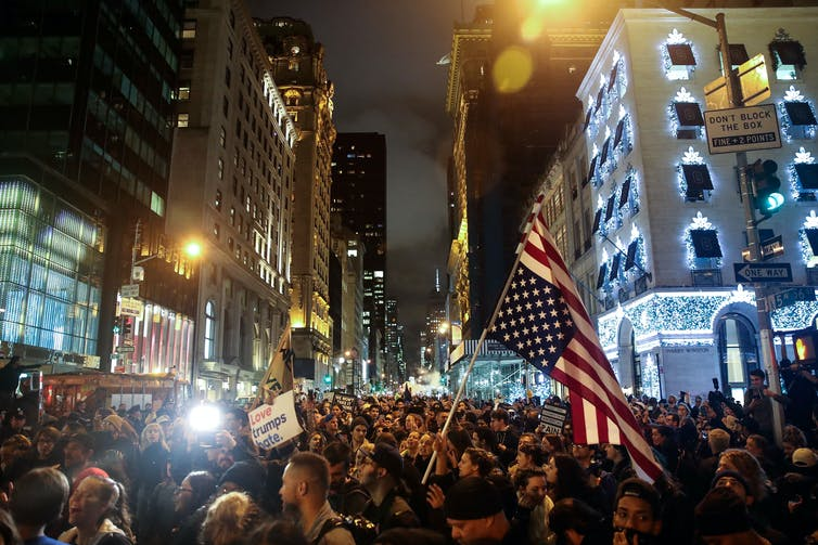 Protesters in NYC at night, holding anti-Trump signs and waving American flags