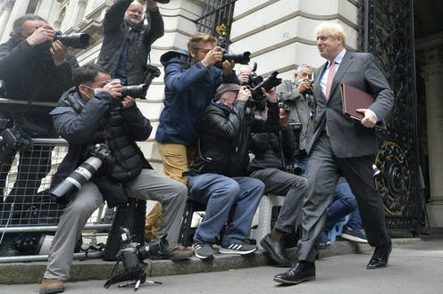 Boris Johnson cheerfully greets the press.