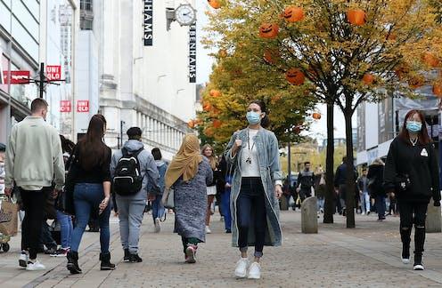 Six people walk down a pedestrianised street.
