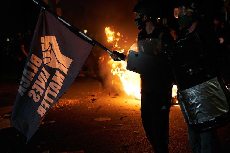 Black Lives Matter protesters near a fire in Portland, Oregon.