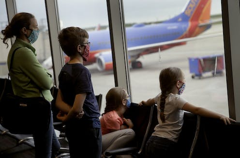 A family waits in an airport with masks on.