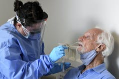 A medical professional inserting a nasal swab into an older man's nose.