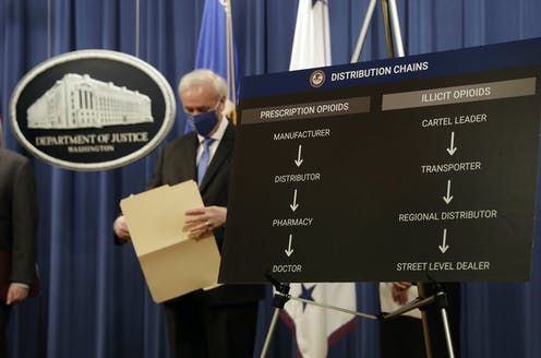 A man in a mask looks down while holding an open file folder at a Justice Department briefing.