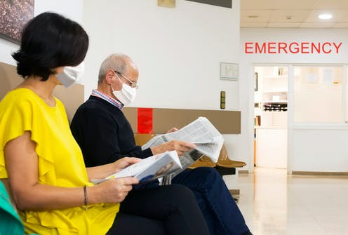 A younger woman and an older man wearing facemasks sit in a waiting room at a hospital.