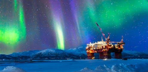 An oil platform in frozen landscape, sky lit by the Northern Lights.