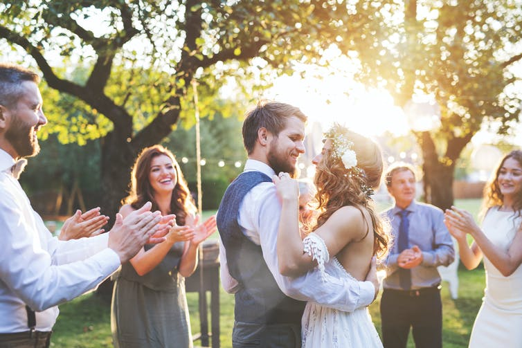 A couple dancing at their outdoor wedding, surrounded by guests clapping.