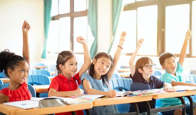 Elementary school children (including Vietnamese children)  raising their hand in class.