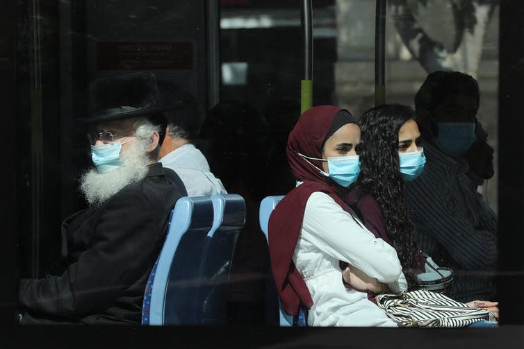 People sitting on a bus with masks in Israel