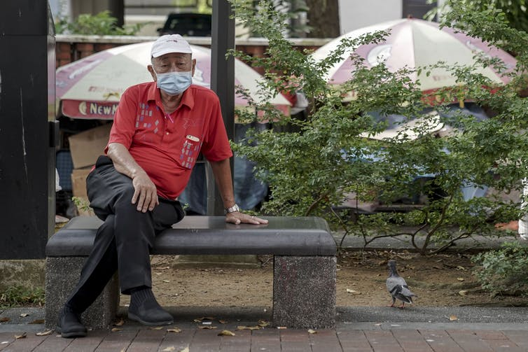 A man sitting on a bench in Singapore, wearing a face mask