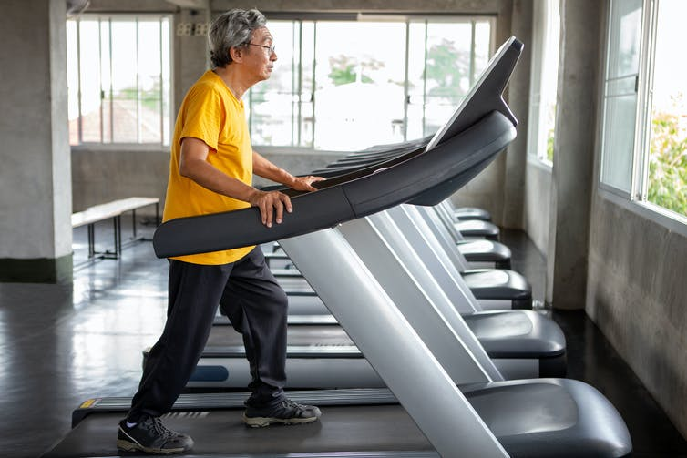Older man walking on a treadmill.