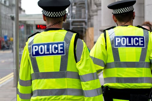 Two UK police officers, seen from behind