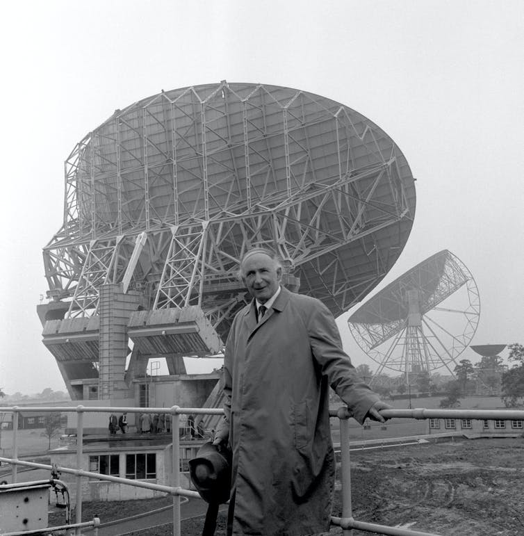 Black and white image of Sir Bernard Lovell in front of the radio telescope.