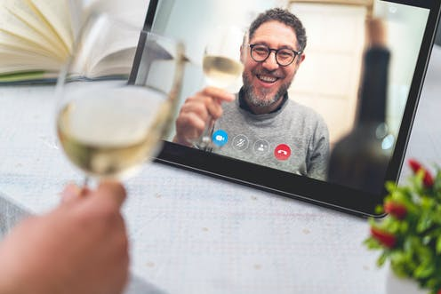 Man on video call screen holding glass of wine