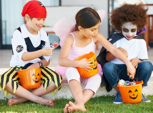 Three children dressed in Halloween costumes holding candy buckets while sitting down.