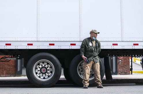 man with lowered mask leans against truck