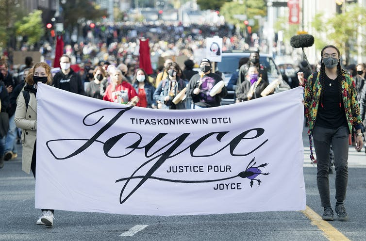 People marching and holding a banner that says Justice for Joyce
