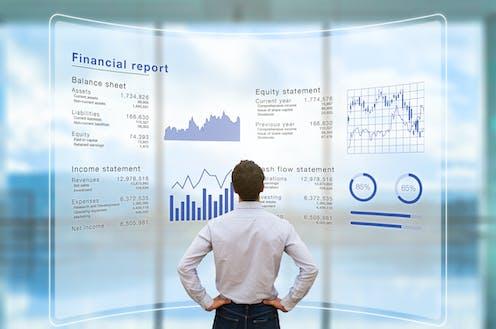 Un hombre en camisa, de espaldas, observa una pantalla que muestra un informe financiero.