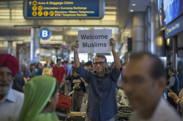 Man holds a sign reading 'Welcome Muslims' in an airport