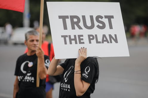 A women in a black tshirt holding a sign reading TRUST THE PLAN